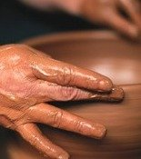 hands shaping a clay pot